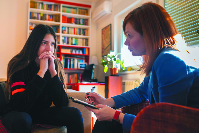 A counsellor talking to a client in an office