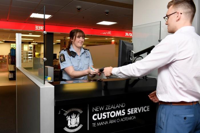 A customs officer at an airport hands a passport to a customer