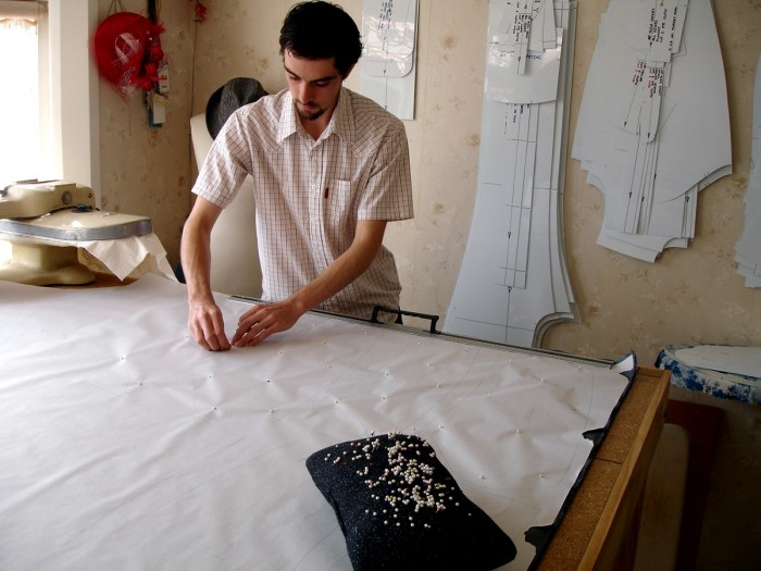 Ra Thomson standing at a workbench pinning pattern to fabric in studio