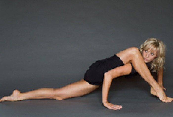 Loren de Boeck in a contorted pose on the floor with one leg over her shoulder