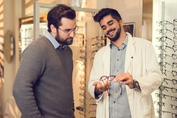 A male dispensing optician recommending a pair of glasses to a customer