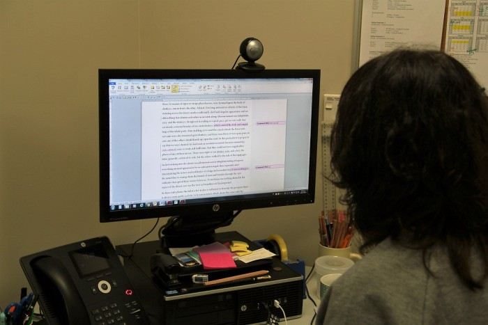 Woman proofreading a book on a computer