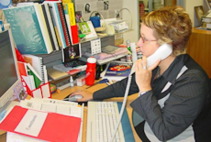 Moana Mackey at her desk, talking on the phone