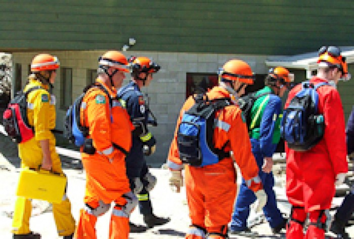 Jan Pryor and colleagues wearing orange suits and hard hats in a training exercise