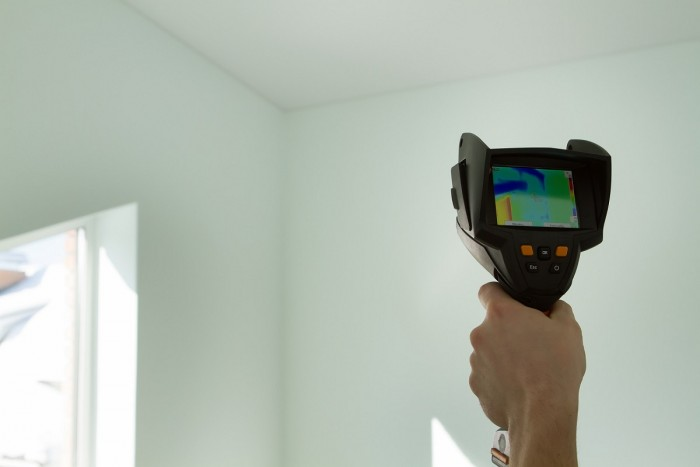 An energy auditor holds up a thermal imaging device to check heat loss in a room
