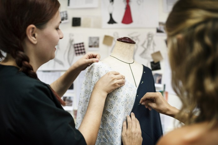 A fashion designer pins fabric on a dress form while a fashion assistant helps