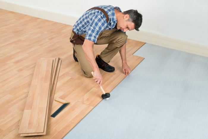 A flooring installer installing laminated hardwood