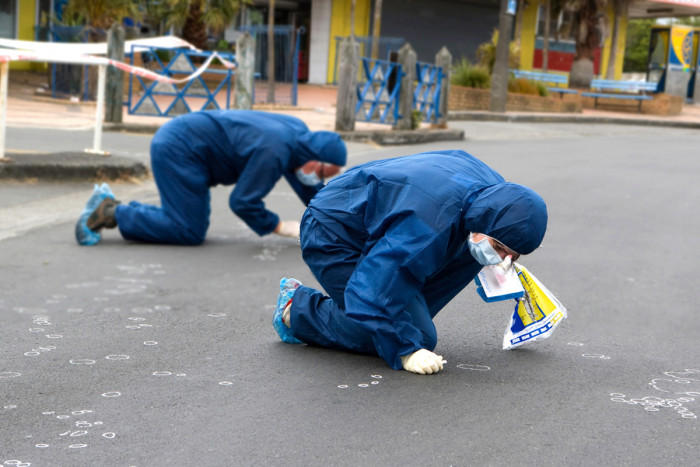 Two scientists kneeling and searching for evidence on the ground