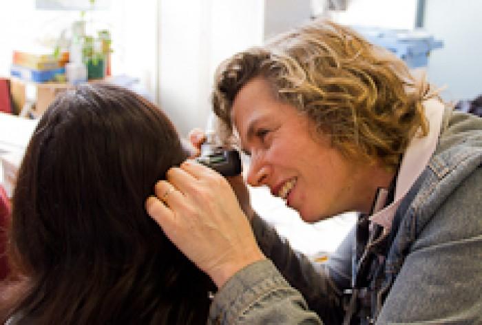 Samantha Murton examining a patient's ear.