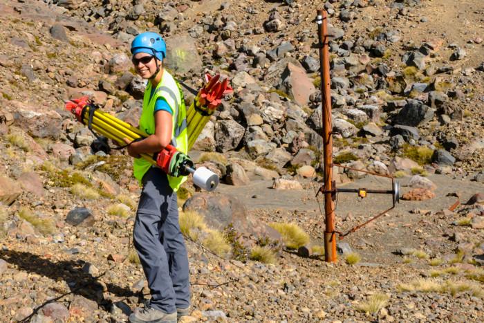 Geophysicist standing on Mt Ruapehu, holding laser-scanning equipment