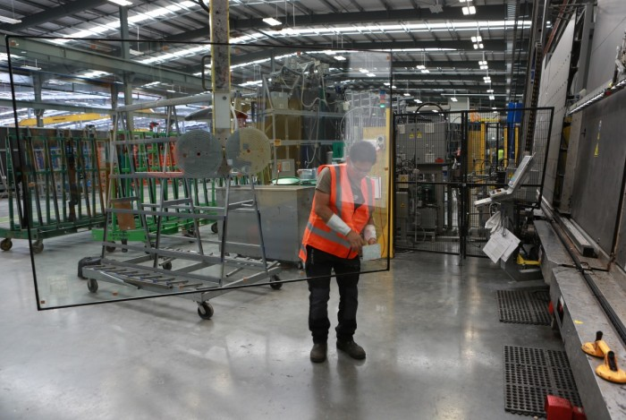 A glass processor using suction pads to move a large piece of double-glazed glass