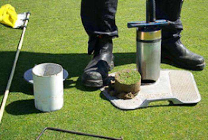Te Kooti Ross repairing the hole on a golf putting green