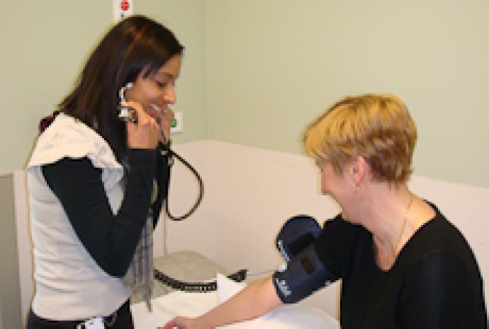 Premjit Gill takes the blood pressure of a patient.