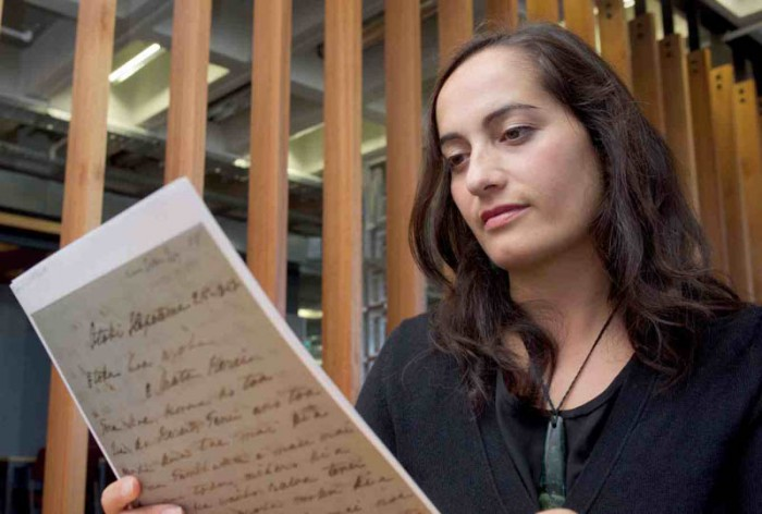 Dr Arini Loader reading a copy of a letter written by a 19th century Māori woman