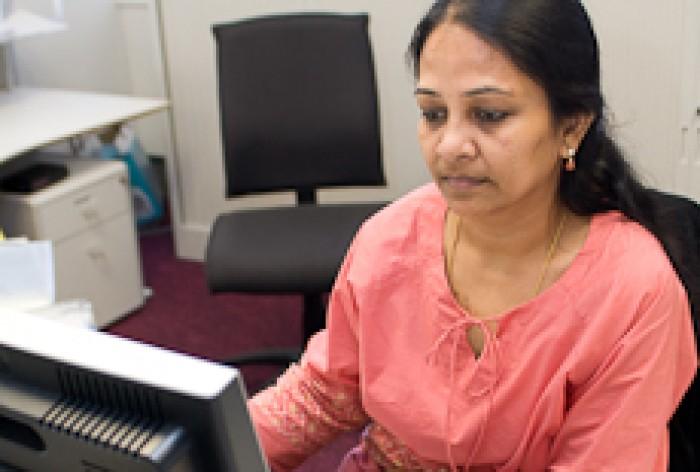 Lakshmi Murali sitting at a computer