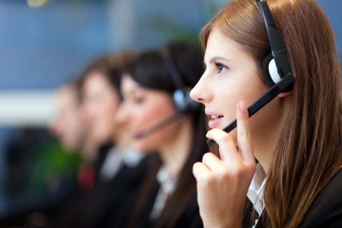 A woman talking into a headset, with three other workers beside her
