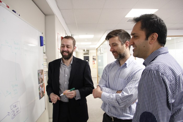 Three men stand at a whiteboard, reading a diagram and smiling