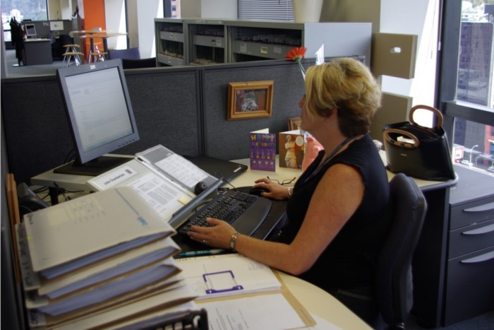 Julie Chamberlain sitting at her computer with a pile of files next to her