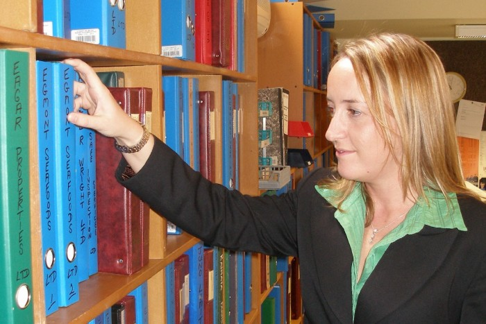 Kim Harrison looks at a shelf of folders