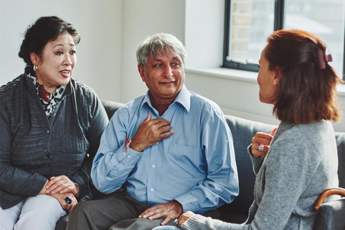 A male interpreter sitting between two women