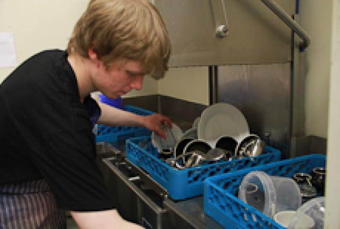 Zak Murdoch emptying dishes from a dishwasher rack
