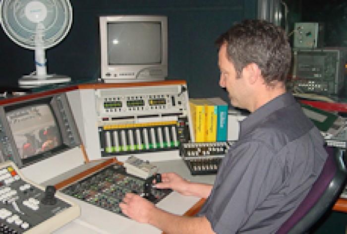 Gavin Jack sitting at a lighting control desk
