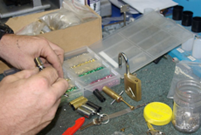 Close-up of a locksmith working with a padlock