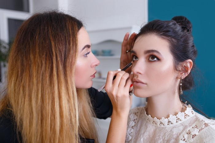 A make-up artist holds a model's head with one hand and applies eyeliner with the other