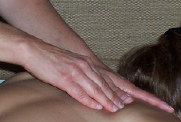 A close-up picture of a massage therapist's hands massaging a client's back.
