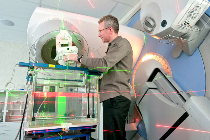 A male medical physicist standing and using a linear accelerator machine