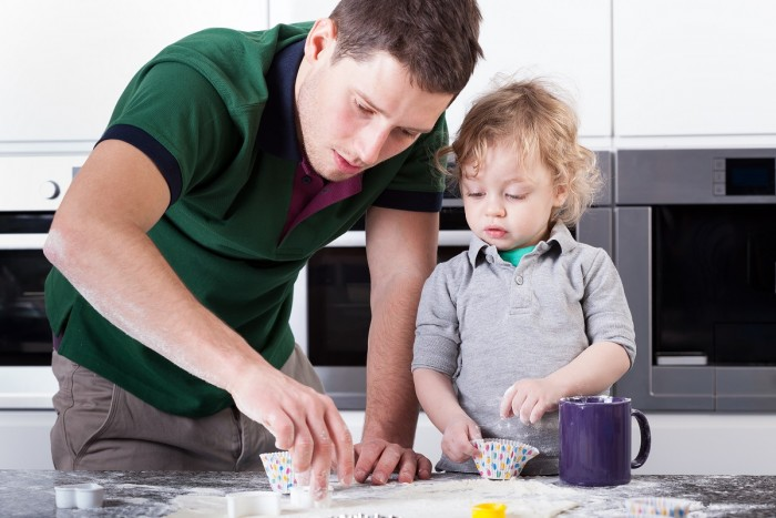 A young man in a home kitchen is showing a toddler boy how to bake cupcakes