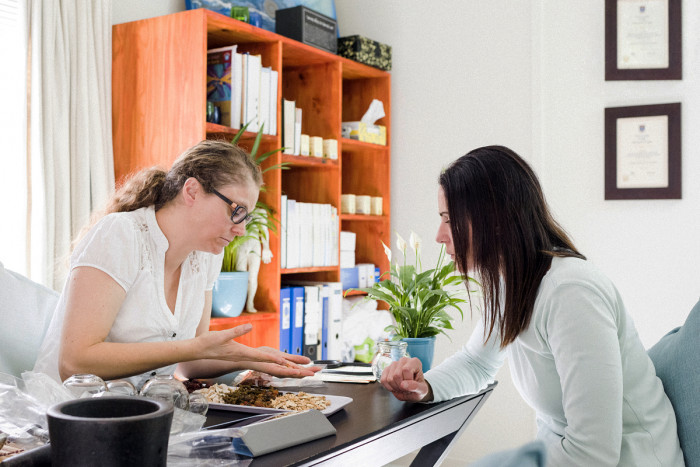 A naturopath explains herbal medicine treatments to a patient