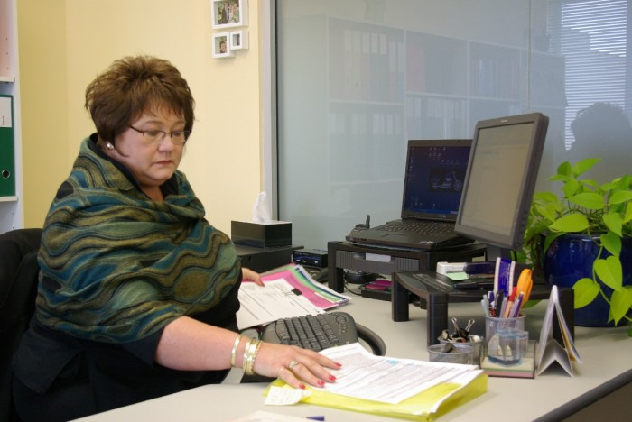 Margie Laubscher sorting out files at her desk