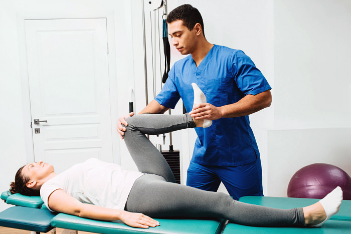 A male osteopath treats a female patient by manipulating her leg muscles and joints