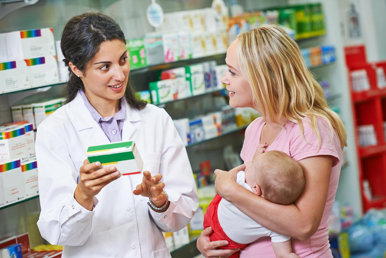 A female pharmacist in a white coat