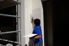 An exterior plasterer applying plaster to a wall