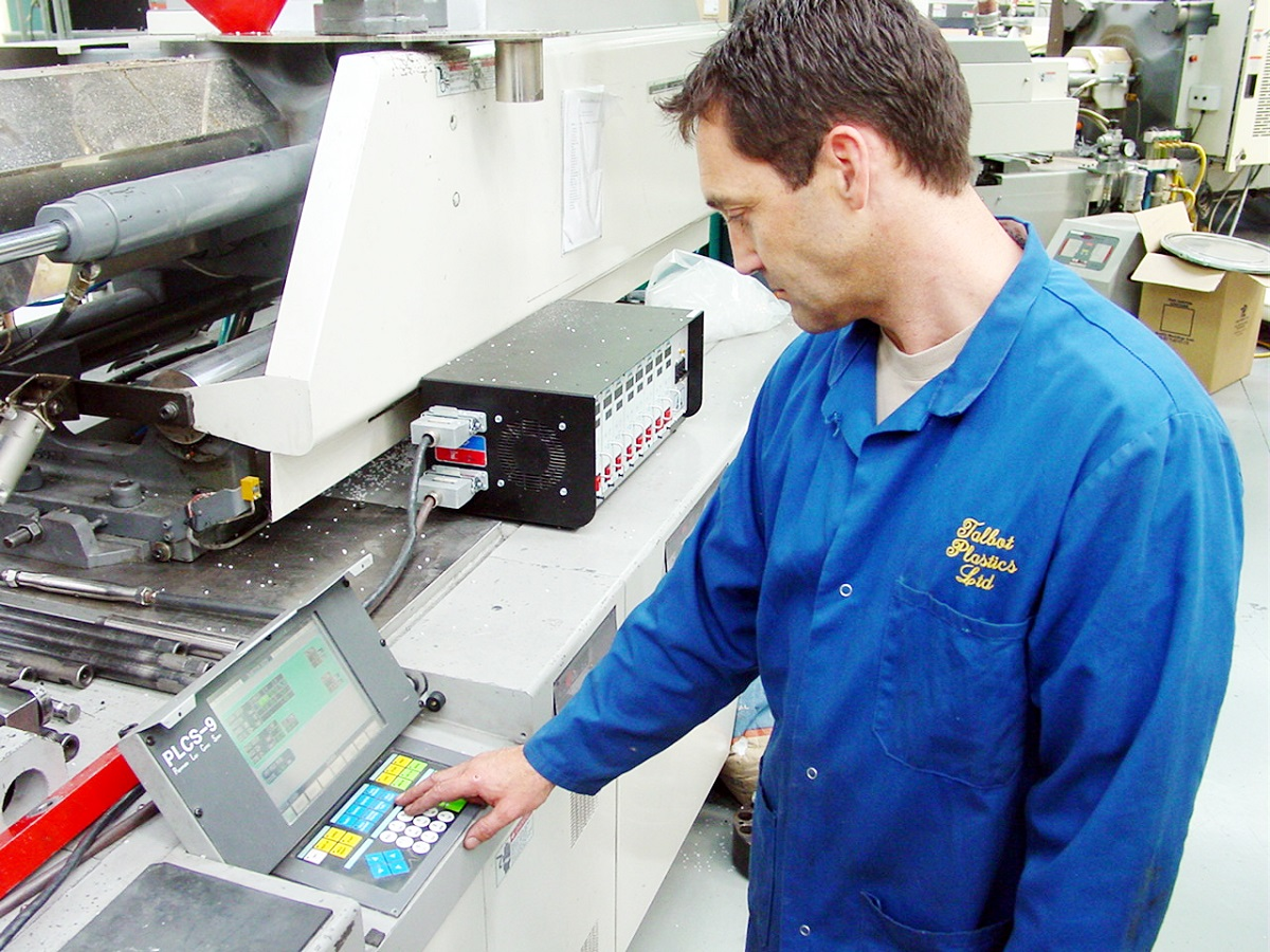 andrew mcleod presses a button on the plastics machine to test that it is working