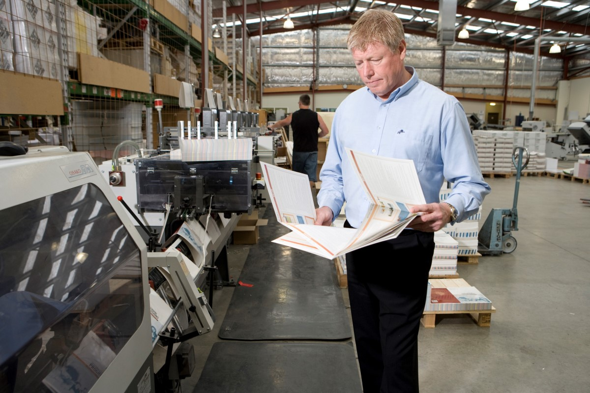 A Print Finisher Standing By Finishing Equipment Looking At Final Product