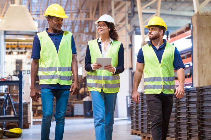A production manager talking to a quality manager and technical manager at a factory