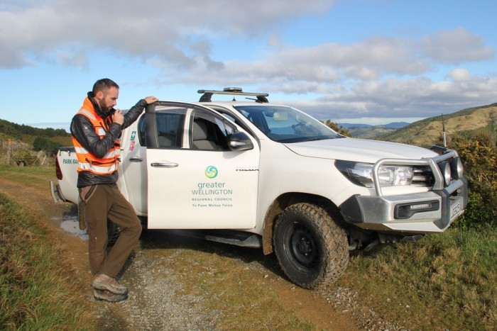 Jeremy Paterson, standing beside a park ranger ute, using a handheld radio