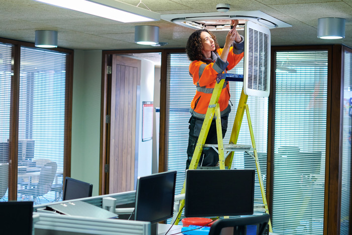 A female air-conditioning technician inspecting an air-conditioning unit in an office