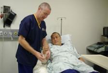 A nurse puts a bandage on a patient's arm