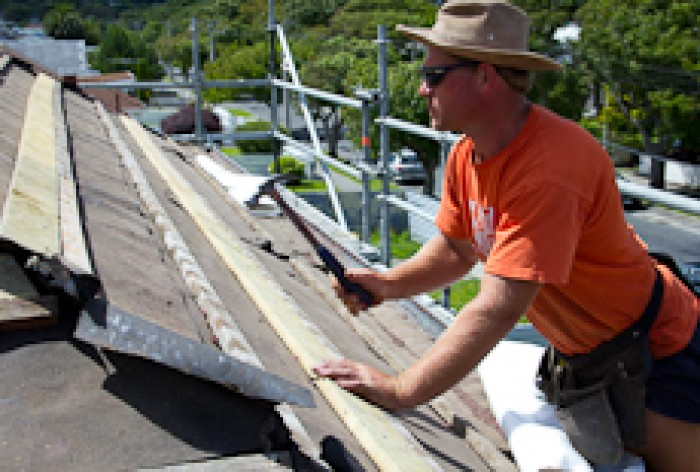 A roofer nailing down a roofing batten
