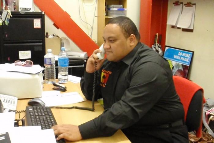 Hopoi Vaivevea seated at a desk talking on the phone