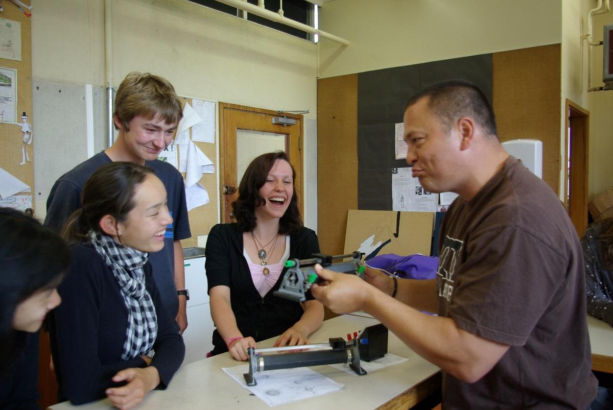 Craig Rofe Talks To Three Students In A Physics Class