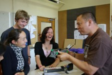 Craig Rofe talks to three students in a physics class