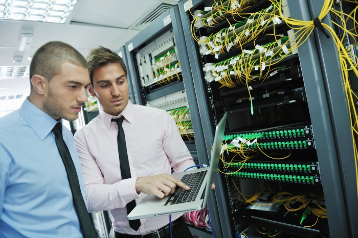 Two men looking at a laptop near a cupboard full of equipment with wires