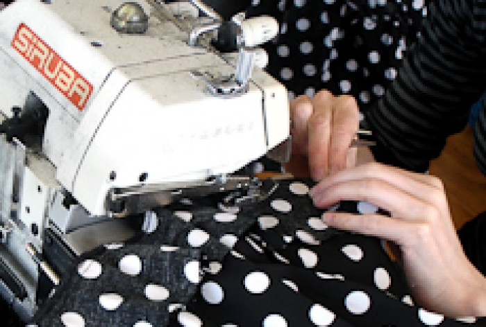 Close up of Angela Flynn guiding black material with white spots through a sewing machine