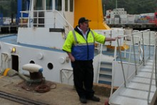 Paul Wilson standing beside the gangplank of his ferry