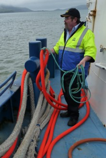 Paul Wilson looking off the side of  his ferry with a rope in his hand